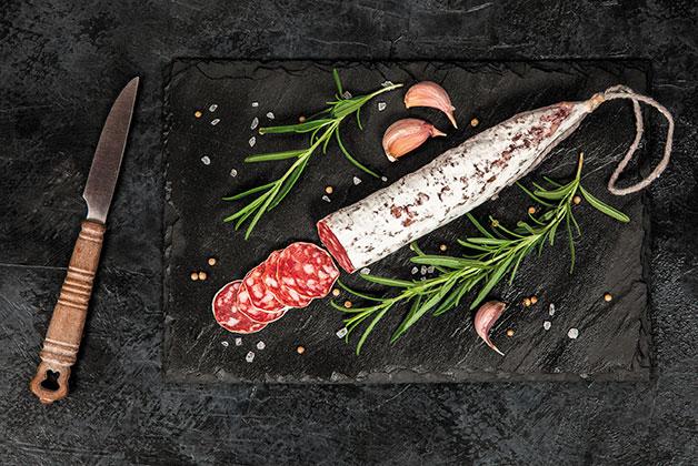 Eine Salami aufgeschnitten auf einer Schiefernplatte