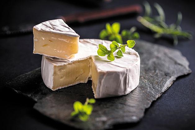 Ein aufgeschnittener Camembert auf einer Schiefernplatte