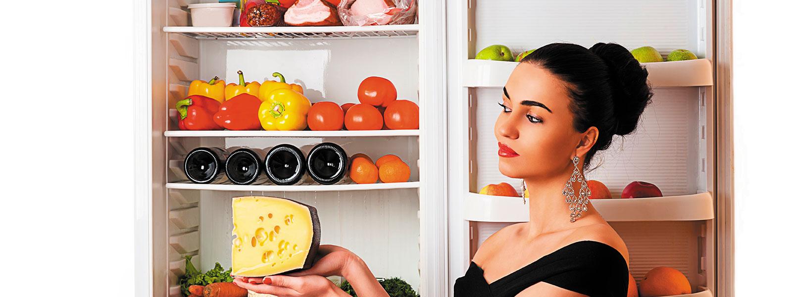 Eine Frau lagert Käse im Kühlschrank