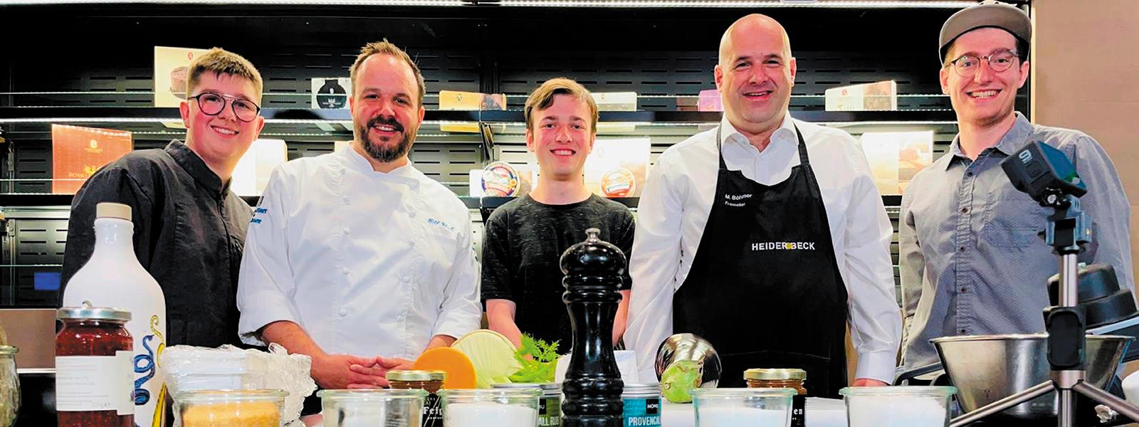 Das Team von Kochen mit Käse posiert an der Theke der Heiderbeck Akademie
