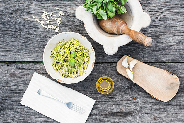 Ein Teller Pasta mit Pesto, dazu Besteck, Pinienkerne und ein Mörser mit Basilikum