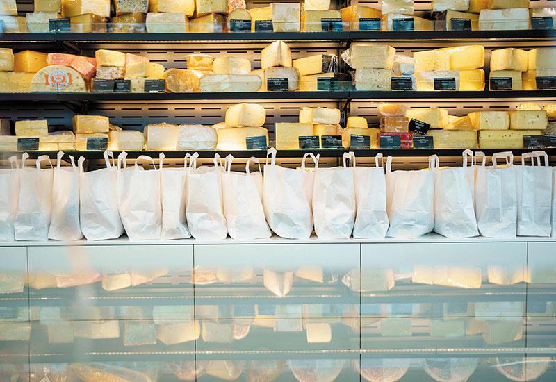 Käsetüten stehen aneinandergereiht auf der Theke des Outlets.